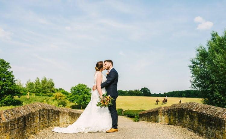 Bride and groom kissing on bridge in Suffolk