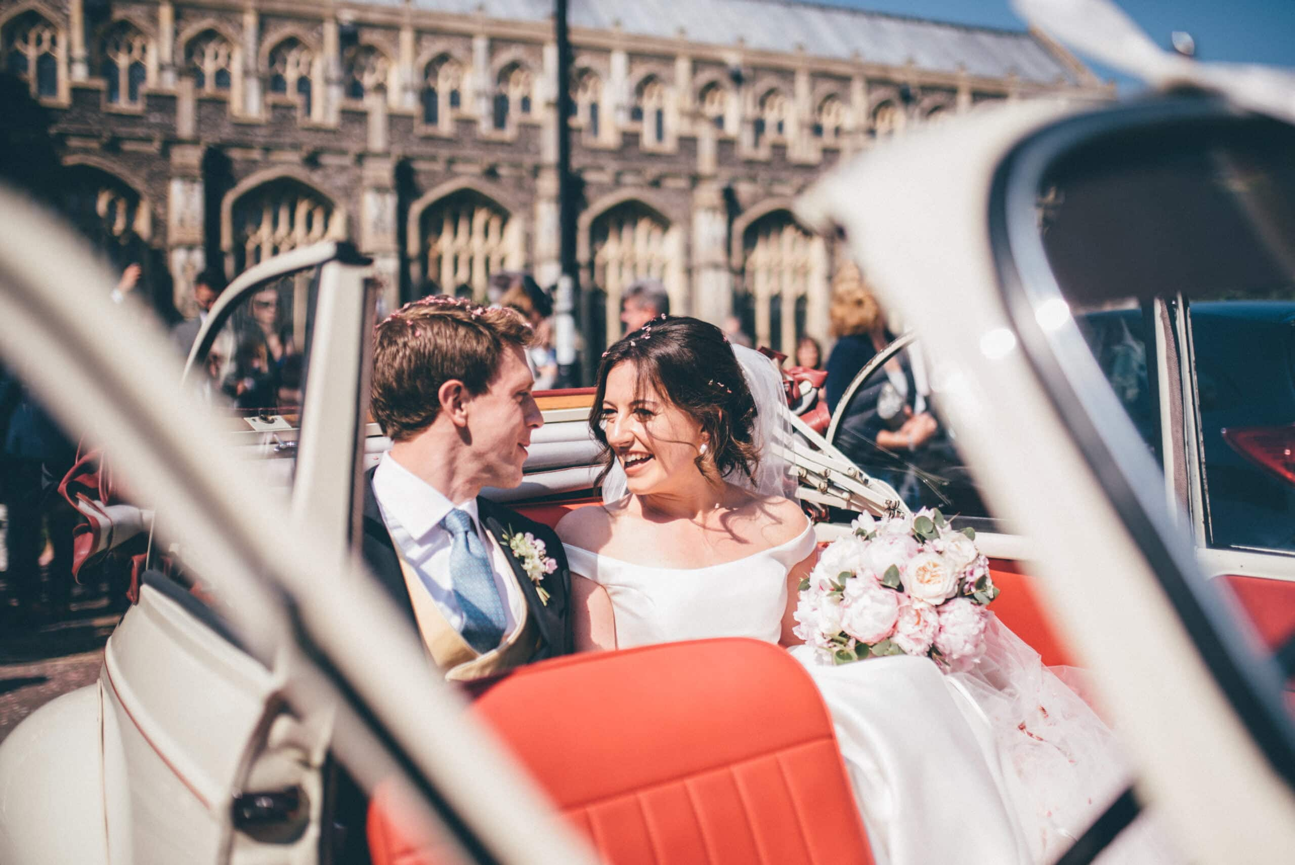 Bride and groom in car after Suffolk church wedding ceremony