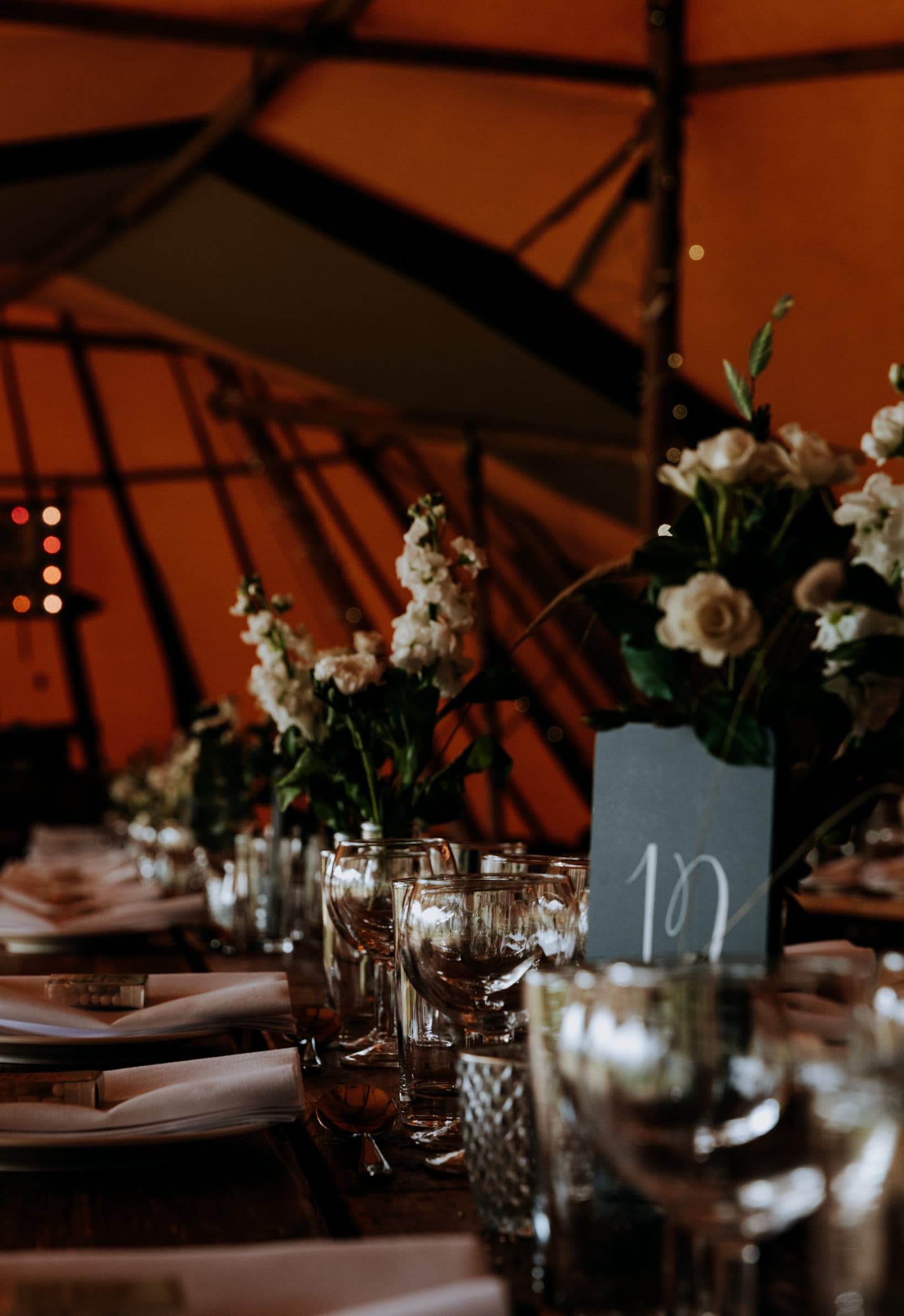 Tipi wedding at Chaucer Barn decorations with hanging foliage and wooden tables